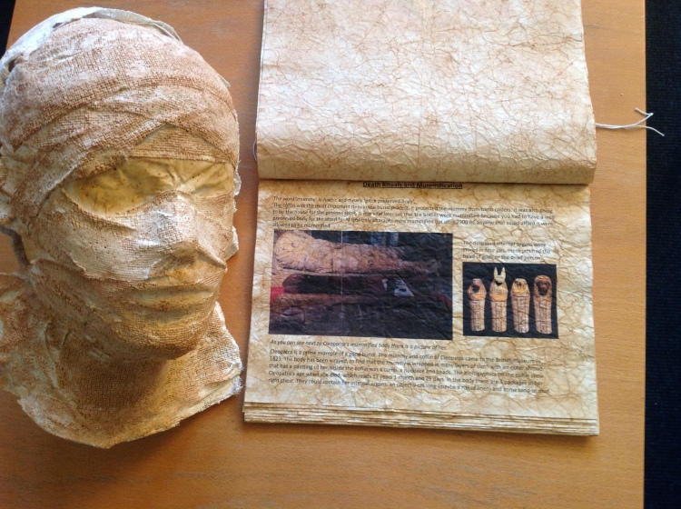Beautifully aged folder about mummification with example mask.