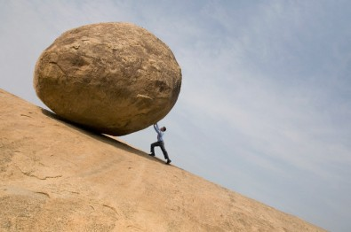 Businessman pushing large rock uphill