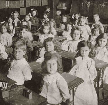 C44WPR Edwardian or Victorian infants sitting at their desks in classroom during a nature lesson using chalk on slate. Early 1900's